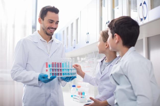 Edukacja w laboratorium. brodaty wesoły mężczyzna trzyma stojak, podczas gdy dziewczyna bierze stamtąd fiolkę i patrzą na niego dzieci