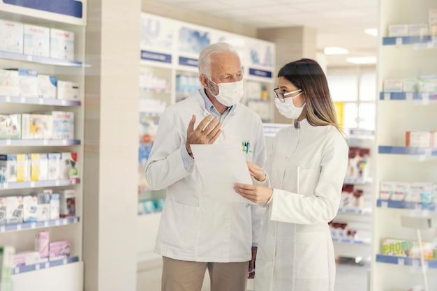 Edukacja w zakresie farmacji i koronawirusa. dojrzały farmaceuta wyjaśnia dokumentację w aptece młodemu farmaceucie w trakcie szkolenia zawodowego. noszą mundury i maski na twarz