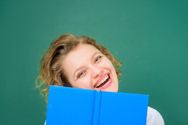 Edukacja z powrotem do szkoły uśmiechnięty nauczyciel z książkami zabawny nauczyciel przedmioty szkolne praca w szkole szczęśliwa