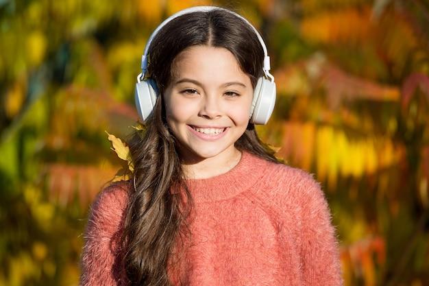 Edukacyjne i do pobrania audiobooki dla dzieci. dziecko dziewczynka relaksuje w pobliżu jesiennego drzewa ze słuchawkami. muzyka na jesienny nastrój. słuchając piosenki. ciesz się muzyką jesienny dzień. jesienne spacery z fajnymi piosenkami.