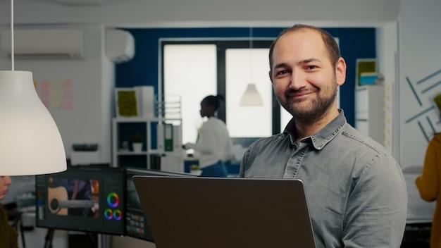 Edytor wideo, pracownik stojący przed kamerą, uśmiechnięty, pracujący w biurze agencji kreatywnej, trzymający la...