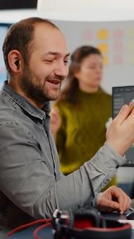 Edytor wideo rozmawiający podczas rozmowy wideo, trzymający film edytujący na smartfonie, siedzący w start-upowej agencji kreatywnej