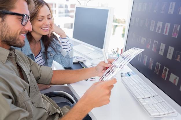 Edytorzy zdjęć szczęśliwie przeglądają arkusz kontaktowy