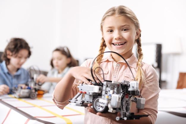 Efekt mojej pracy. zachwycona uśmiechnięta, celowa dziewczyna stojąca w szkole i trzymająca robota elektronicznego, podczas gdy jej koledzy pracują nad projektem