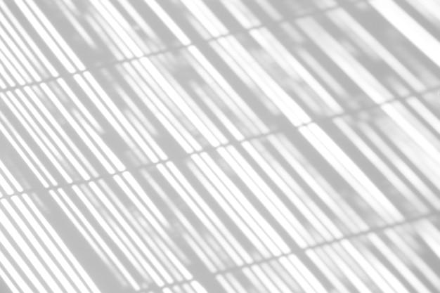 Efekt nakładki cienia. cienie od żaluzji, okna i cienkiego ekranu na czystej białej ścianie w słoneczną pogodę.