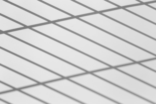 Efekt nakładki cienia. cienie z linii siatki lub kraty ogrodzenia lub poręczy na czystej białej ścianie w słoneczny, pogodny dzień. geometryczne cienie