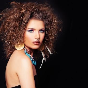 Efektowna kobieta na ciemnym tle akcesoria do makijażu po trwałej fryzurze