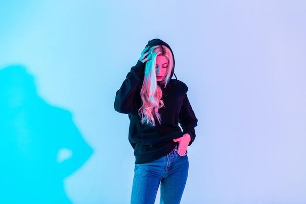 Efektowna piękna młoda blondynka w modnej czarnej bluzie nosi kaptur w niebieskich dżinsach na kolorowym neonowo różowym jasnym tle w studio