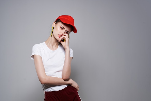Efektowne kobieta w czerwonej czapce lato moda ozdoba pozowanie jasnym tle. zdjęcie wysokiej jakości