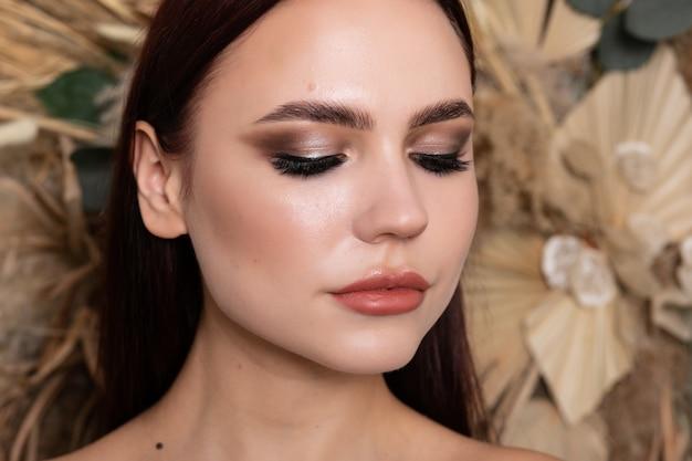 Efektowny portret pięknej modelki ze świeżym makijażem dziennym i romantyczną falistą fryzurą. modny błyszczący rozświetlacz na skórze, seksowny makijaż błyszczyka i ciemne brwi