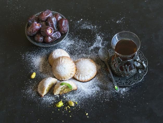 """Egipskie ciasteczka """"kahk el eid"""" z datami i filiżanką herbaty podawane na czarnym stole. ciastka z islamskiej uczty el fitr."""