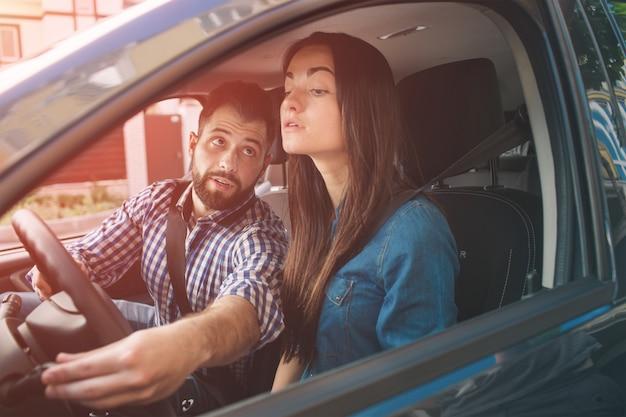 Egzamin na prawo jazdy. młoda poważna kobieta prowadząca samochód czuje się niedoświadczona, nerwowo patrzy na ruch drogowy, szukając informacji w celu podjęcia właściwych decyzji. człowiek jest instruktorem, kontroluje i sprawdza