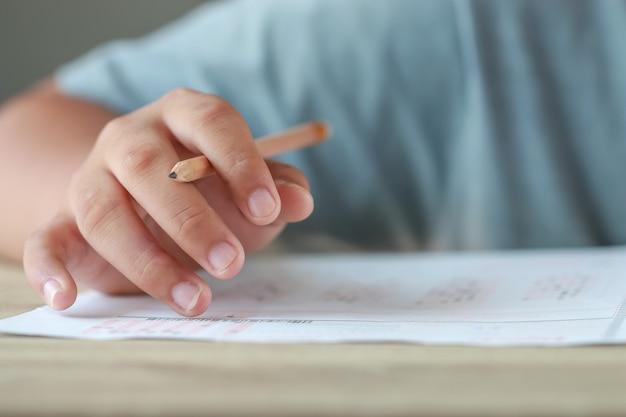 Egzamin testowy edukacji w koncepcji szkoły: student uniwersytetu trzymający papier do notatek ołówkowych na arkuszu odpowiedzi na krześle wykładowym do egzaminów w klasie egzaminacyjnej. uczenie się oceniania w pomysłach klasowych