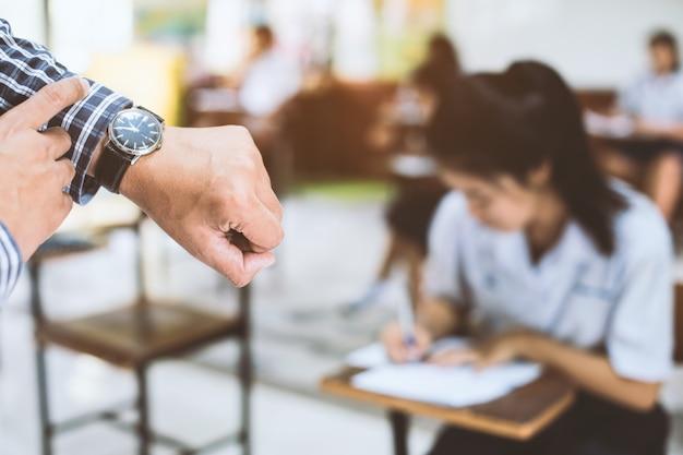 Egzaminatorzy oglądają czas w teście końcowym.