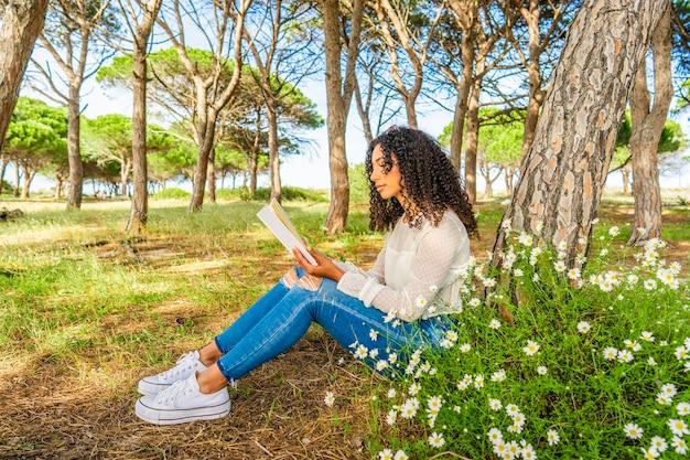 Egzotyczna czarna latynoska dziewczyna siedzi w sosnowym lesie wśród kwitnących stokrotek, czytając preferowaną książkę romansową. kręcona młoda afroamerykanka spędzająca czas na łonie natury z pasją do powieści miłosnych
