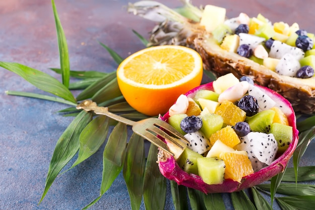 Egzotyczna owocowa sałatka słuzyć w połówce smok owoc i ananas z palmowym liściem na kamiennym tle