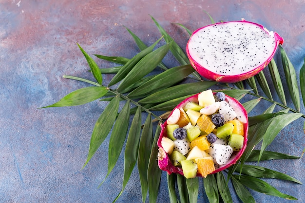 Egzotyczna owocowa sałatka słuzyć w połówce smok owoc na palmowych liściach na kamiennym tle, kopii przestrzeń
