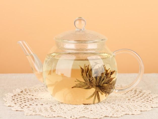 Egzotyczna zielona herbata z kwiatami w szklanym czajniczku na stole na kolorowej powierzchni. proces robienia herbaty