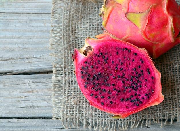 Egzotyczne dojrzałe różowe owoce pitaya lub dragon. czerwona pitahaya tropikalna owoc ciie na pół na starym drewnianym stole selekcyjna ostrość.