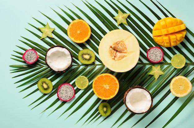 Egzotyczne owoce i liście palm tropikalnych - papaja, mango, ananas, banan, karambola, smok owoc, kiwi, cytryna, pomarańcza, melon, kokos, wapno.