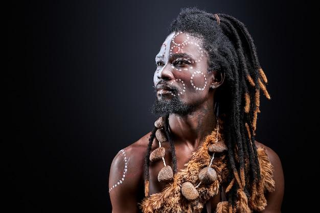 Egzotyczny aborygen z etnicznym makijażem na twarzy, mężczyzna bez koszuli z dredami