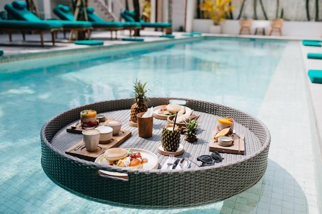 Egzotyczny obiad w hotelu. odkryty strzał tabeli z owocami w basenie.