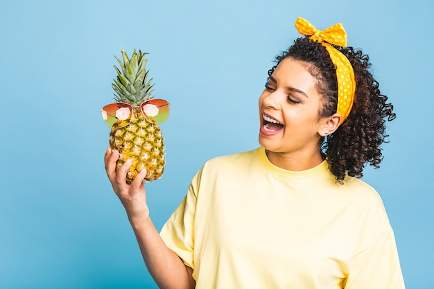 Egzotyczny pomocnik ananasa w diecie. afroamerykanin czarna ciemnoskóra wesoła dziewczyna trzyma w dłoniach ananas na białym tle na niebieskim tle.