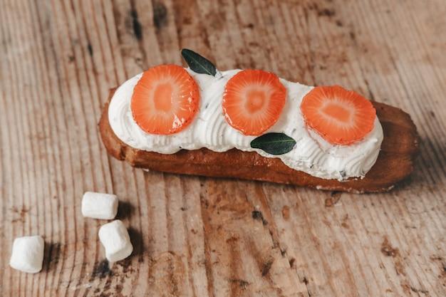 Ekler z bitą śmietaną i kawałkami truskawek i mięty. estetyka słodkiego ciasta. słodki stół jesienią. deser na rozweselenie