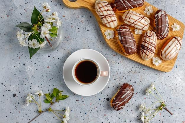 Eklery lub profiteroles z czarną czekoladą i białą czekoladą z kremem w środku, tradycyjny francuski deser. widok z góry.