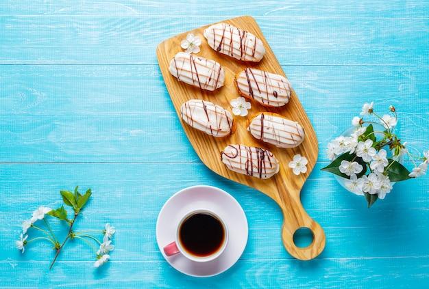 Eklery lub profiteroles z czarną czekoladą i białą czekoladą z kremem w środku, tradycyjny francuski deser.