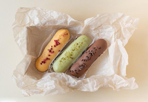 Eklery na tle papieru rzemiosła. martwa natura cześć deser nastroju. tradycyjny francuski deser z kolorowym lukrem. koncepcja pieczenia, przepisy kulinarne, baner piekarniczy, reklama kawiarni.