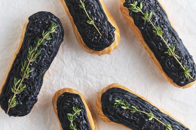 Eklery z kremem pistacjowym i czarnym lukrem. ciasta ozdobione gałązkami tymianku. deser na białym stole w kuchni.