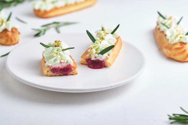 Eklery z kremem pistacjowym i nadzieniem malinowym, doprawione kruszoną pistacjami i rozmarynem.