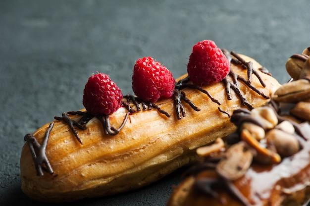 Eklery z orzeszkami ziemnymi, polewą czekoladową i malinami
