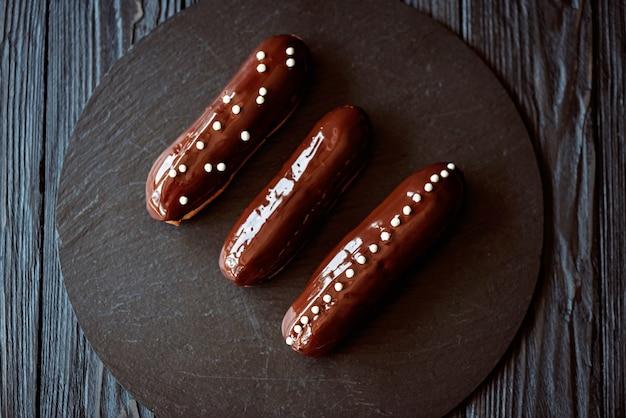 Eklery z polewą z ciemnej czekolady i kroplami na ciemnym talerzu na ciemnym tle widok z góry