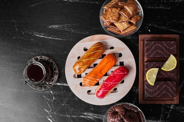 Eklery z sosami owocowymi na wierzchu podawane z herbatą i ciastkami.