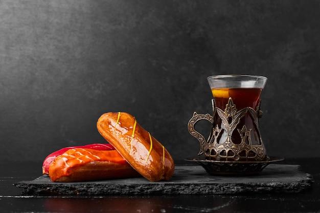 Eklery z sosami owocowymi na wierzchu podawane ze szklanką herbaty.