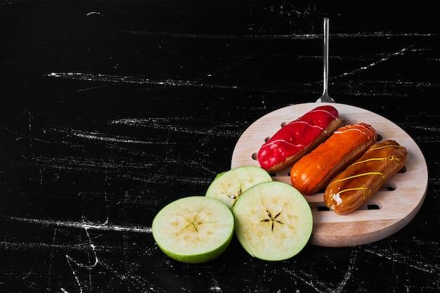 Eklery z sosami owocowymi na wierzchu.