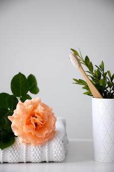 Eko bambusowa szczoteczka do zębów w białym uchwycie i pastelowa pomarańczowa róża na białym ręczniku