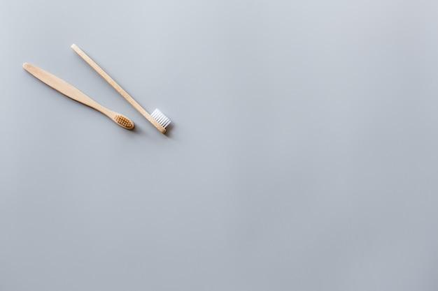 Eko naturalne bambusowe szczoteczki do zębów płaskie leżał na szarym tle