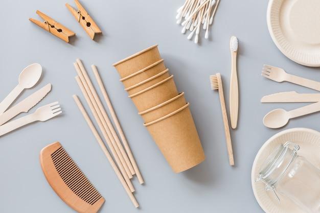 Eko naturalne papierowe kubki, słomki, drewniane sztućce leżały na szaro