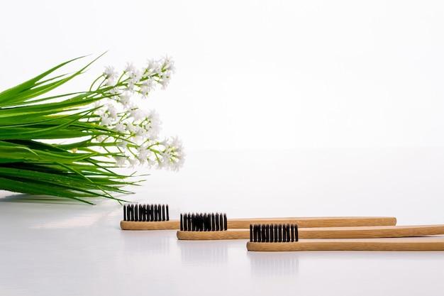 Eko szczoteczki do zębów wykonane z drewna na stole z zieloną gałązką