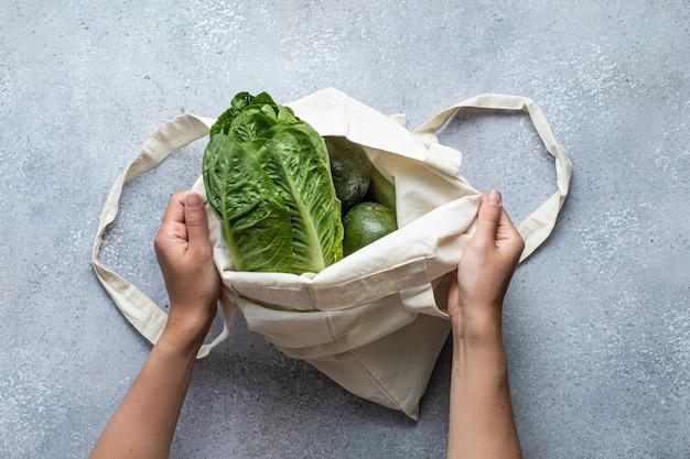 Eko torba i zielone warzywa. tło zdrowej żywności. leżał płasko. zrównoważony styl życia.