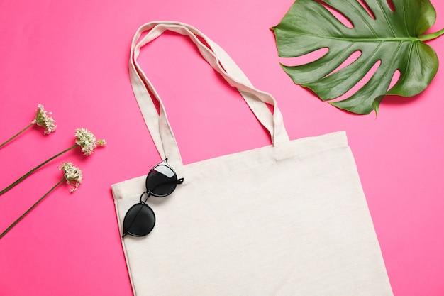 Eko torba, liść palmowy, okulary przeciwsłoneczne i allium na kolor tła