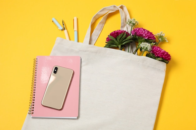 Eko torba, telefon, allium i chryzantema na kolor tła