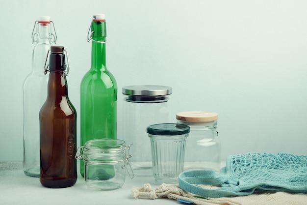 Eko torby, szklane butelki wielokrotnego użytku i słoiki na stole. zrównoważony styl życia. koncepcja zero zakupów i przechowywania artykułów spożywczych