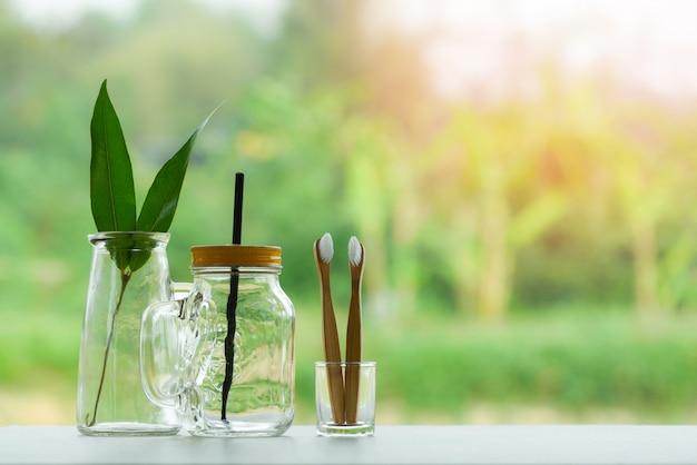 Eko zielony liść w szklanym słoju z dzbankiem ze słomy i bambusową szczoteczką do zębów