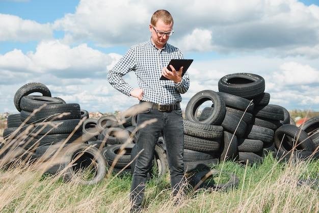 Ekoaktywista na wysypisku zużytych opon samochodowych oblicza szkody w środowisku