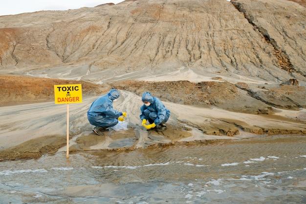 Ekolodzy w gumowych rękawiczkach i butach, osłonach ochronnych i respiratorach, pobierający próbki toksycznej gleby i wody na zanieczyszczonym terenie na wzgórzach