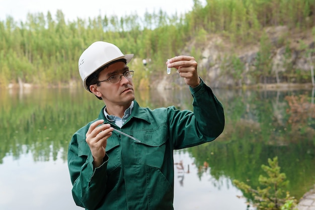 Ekolog lub hydrolog ocenia reakcję próbki wody z jeziora zalanego kamieniołomu